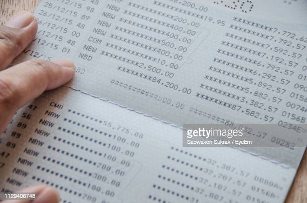 close-up of person holding bank account book - bank account stock pictures, royalty-free photos & images