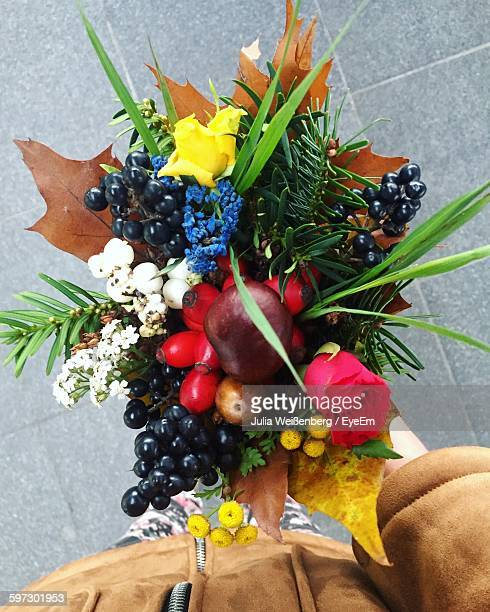 Close-Up Of Person Holding Bouquet Of Fruits And Flowers On Street