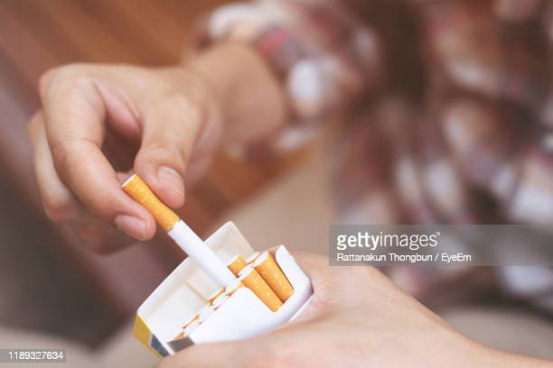 close-up of person holding cigarette pack - cigarette stock pictures, royalty-free photos & images