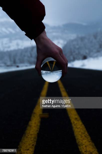 Close-Up Of Person Holding Crystal Ball