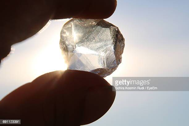 close-up of person holding diamond against sky - diamond gemstone stock pictures, royalty-free photos & images