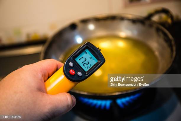 close-up of person holding digital thermometer by cooking oil in container on burning stove - digital thermometer ストックフォトと画像