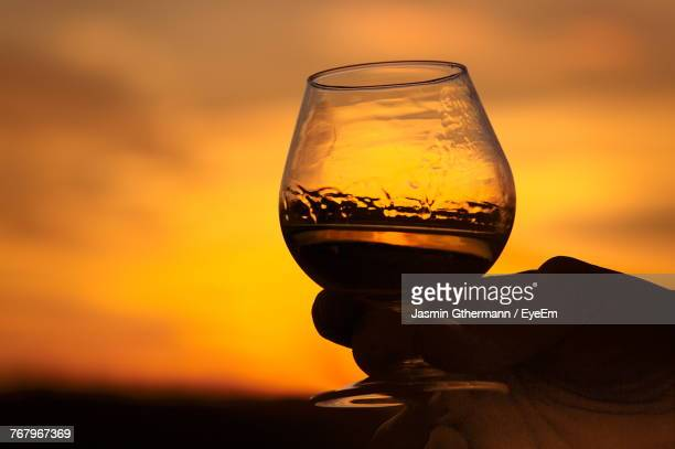 Close-Up Of Person Holding Drink Against Orange Sky