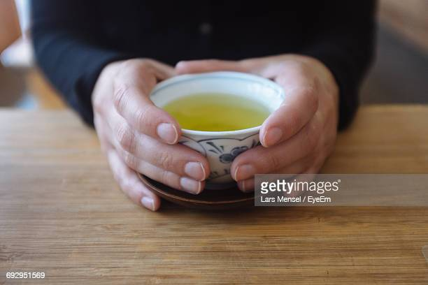 Close-Up Of Person Holding Green Tea On Wooden Table