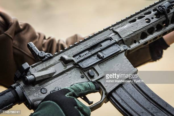 close-up of person holding gun - machine gun stock pictures, royalty-free photos & images