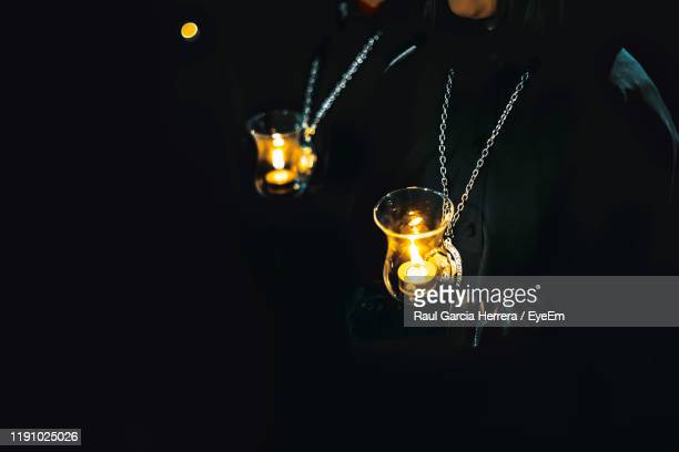 close-up of person holding illuminated light bulb in darkroom - zamora stock pictures, royalty-free photos & images