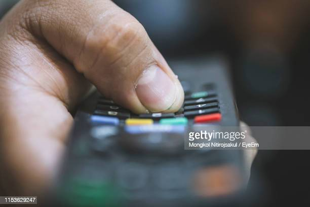 close-up of person holding remote control - remote control stock pictures, royalty-free photos & images