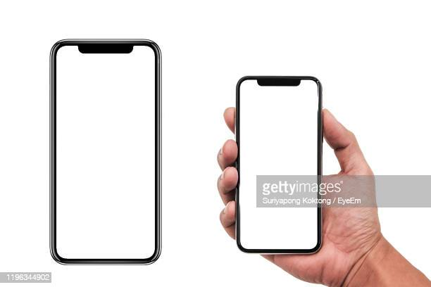 close-up of person holding smart phone against white background - menselijke hand stockfoto's en -beelden