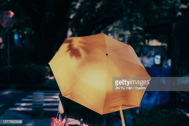 close-up of person holding umbrella - obscured face stock pictures, royalty-free photos & images