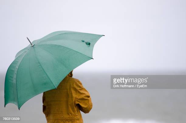 close-up of person holding umbrella - umbrella stock pictures, royalty-free photos & images