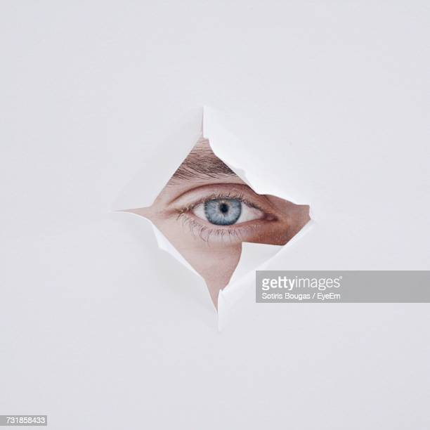 Close-Up Of Person Looking Through Torn White Paper