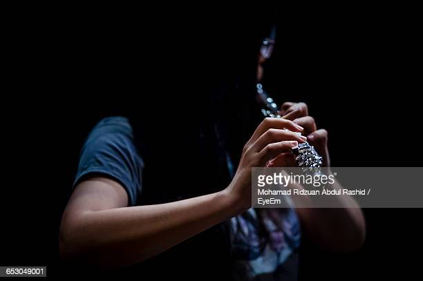 close-up of person playing flute against black background - orchestra stock pictures, royalty-free photos & images