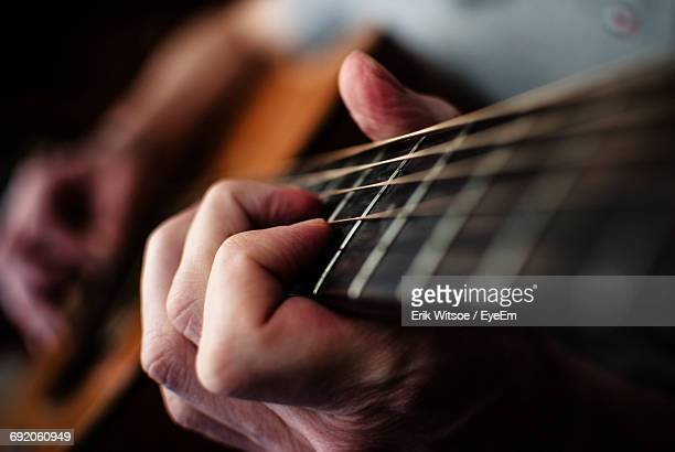 close-up of person playing guitar - gitarre stock-fotos und bilder
