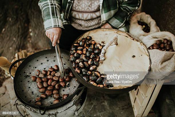 close-up of person roasting chestnuts - castanhas imagens e fotografias de stock