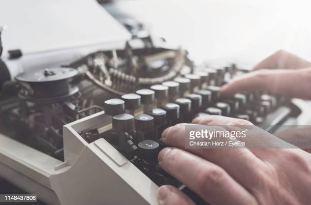 close-up of person using typewriter - écrivain photos et images de collection