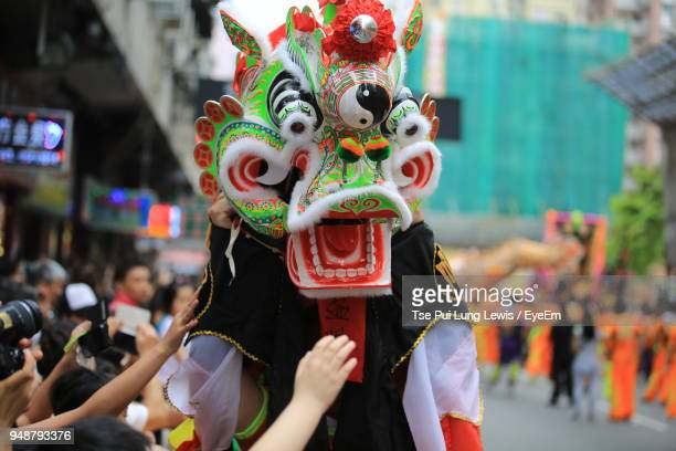 close-up of person wearing costume in city during event - chinese dragon stock pictures, royalty-free photos & images