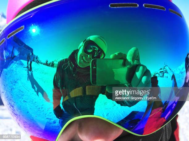 close-up of person wearing ski goggles with reflection of man photographing with mobile phone - fotohandy stock-fotos und bilder
