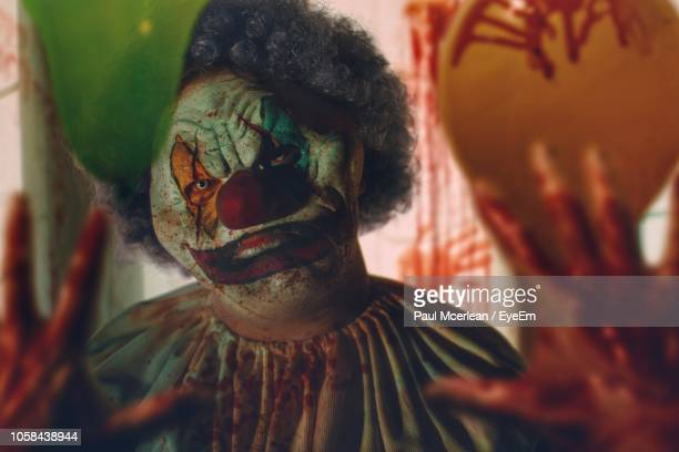close-up of person with clown mask reflecting on mirror - scary clown stock photos and pictures