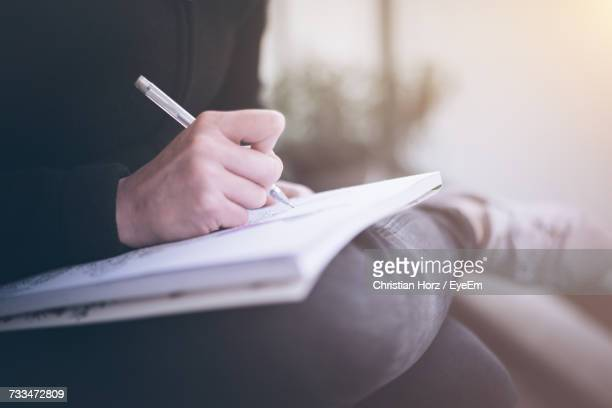 close-up of person writing in book - writing stock pictures, royalty-free photos & images