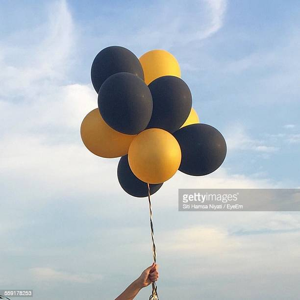 Close-Up Of Persons Hand Holding Balloons