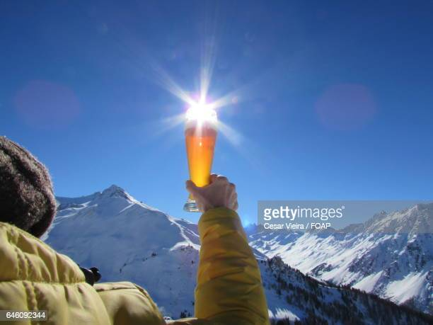 Close-up of person's hand holding beer glass against sunlight