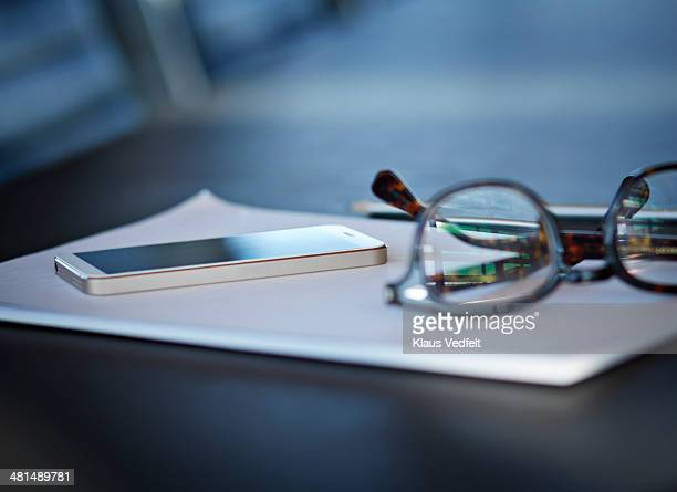 Close-up of phone and glasses on table