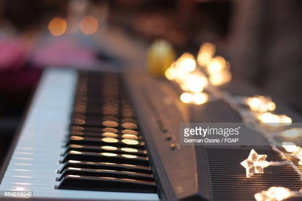 Close-up of piano keyboard with christmas lights