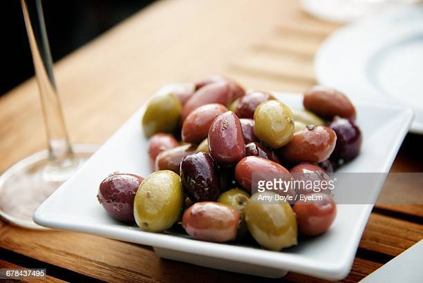 close-up of pickled olives in tray on table - kalamata olive stock pictures, royalty-free photos & images