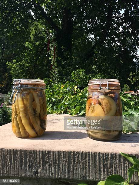 Close-Up Of Pickles In Mason Jars At Yard Against Plants