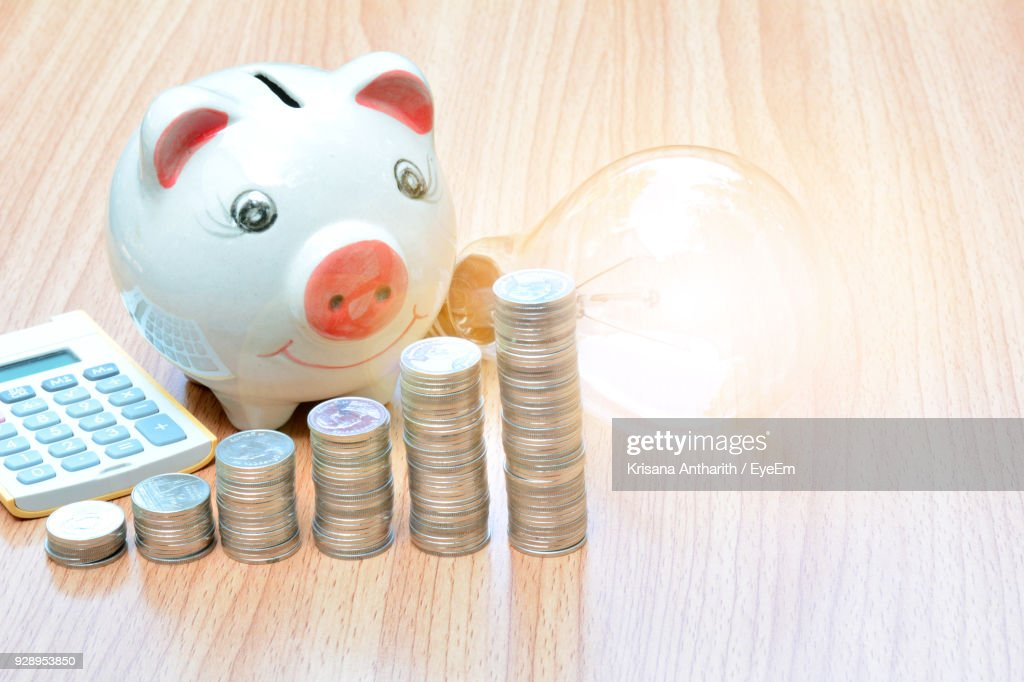 Close Up Of Piggy Bank And Coins By Light Bulb On Table Stock Photo