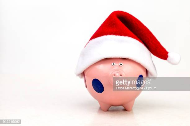 close-up of piggy bank with santa hat over white background - santa hat stock photos and pictures