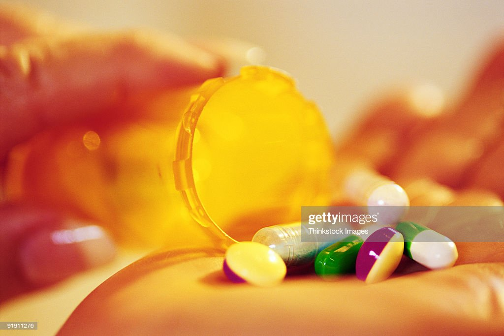 Close-up of pills being poured from bottle into hand : Stock Photo