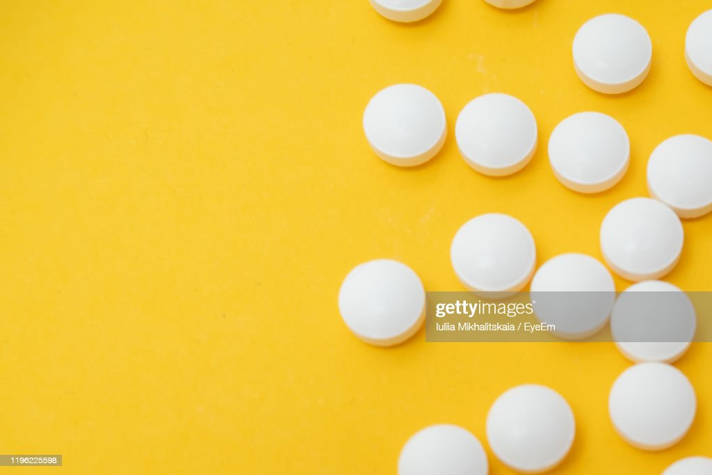 Close-Up Of Pills Over Yellow Background : Stock Photo