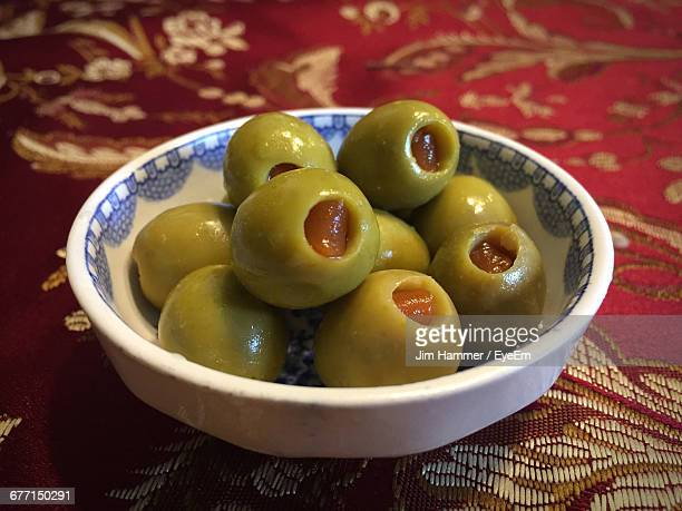 close-up of pimento stuffed olives in bowl on table - olive pimento stock photos and pictures