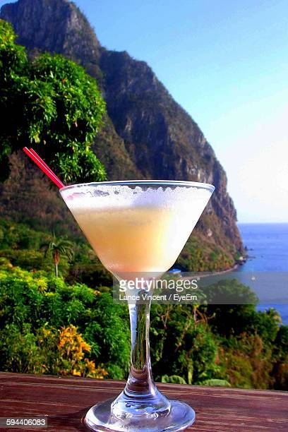 Close-Up Of Pina Colada On Retaining Wall Against Rocky Mountain