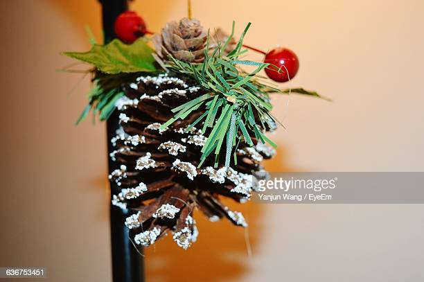 Close-Up Of Pine Cone On Christmas Tree Against Wall