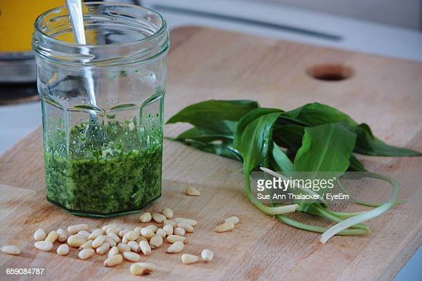 Close-Up Of Pine Nuts And Ramsons By Pesto In Jar On Cutting Board