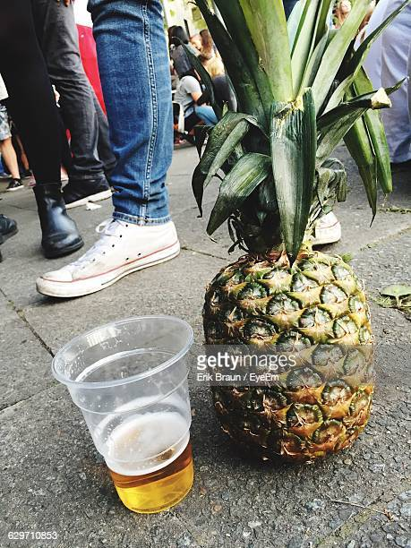 Close-Up Of Pineapple And Beer On Sidewalk