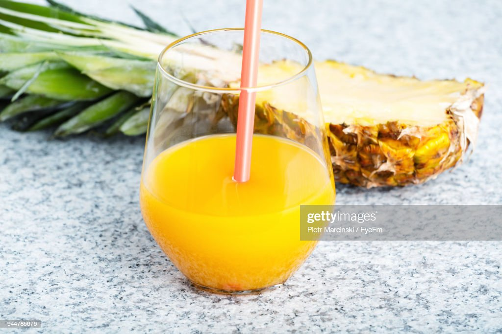 Close-Up Of Pineapple Juice In Glass On Table : Stock Photo