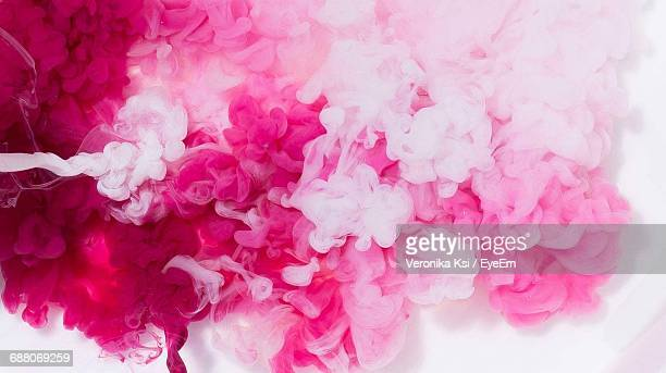 close-up of pink and white ink dissolving in water - mixing stock pictures, royalty-free photos & images