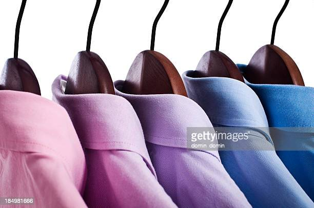 Close-up of pink, blue button down shirts hanging on hangers
