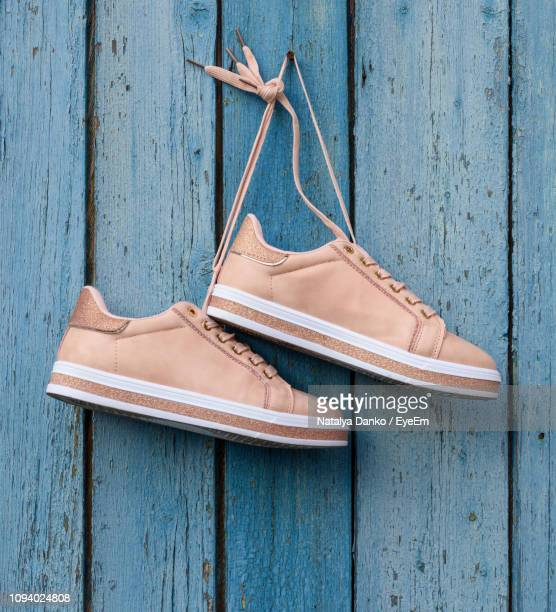 Close-Up Of Pink Canvas Shoes Hanging On Blue Wooden Wall