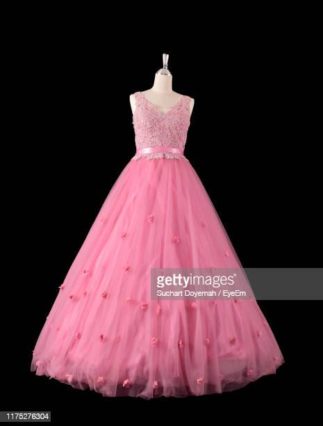 close-up of pink dress on mannequin against black background - evening gown stock pictures, royalty-free photos & images