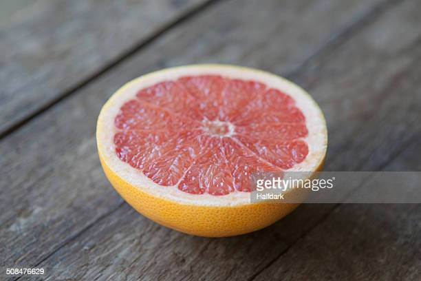 Close-up of pink grapefruit on wooden table