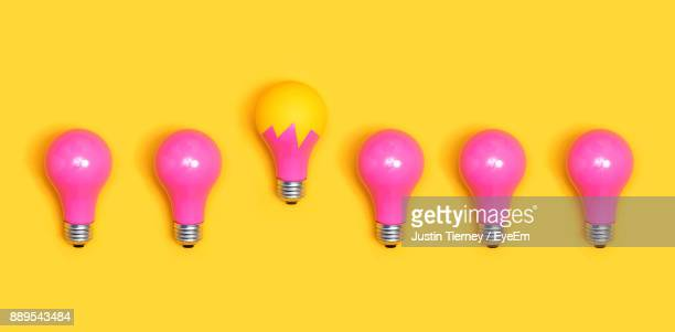 close-up of pink light bulbs over yellow background - light bulb stock pictures, royalty-free photos & images