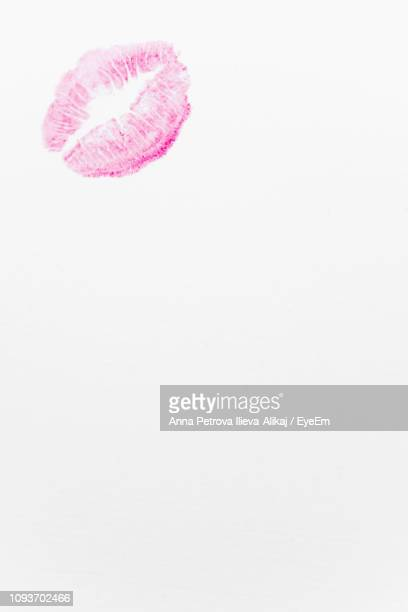 close-up of pink lipstick kiss on white background - キスマーク ストックフォトと画像