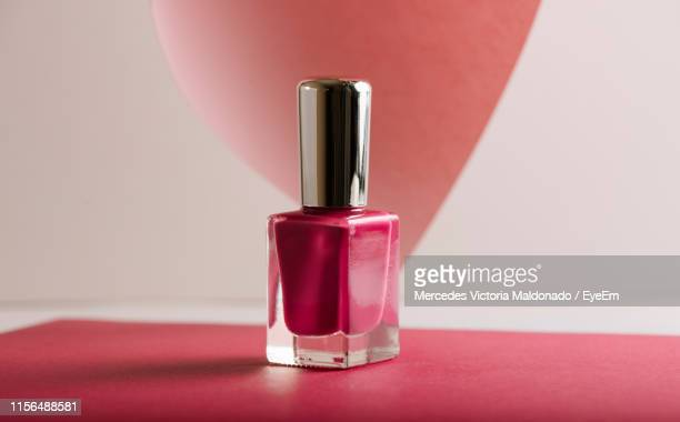 close-up of pink nail polish on table against wall - マニキュア液 ストックフォトと画像