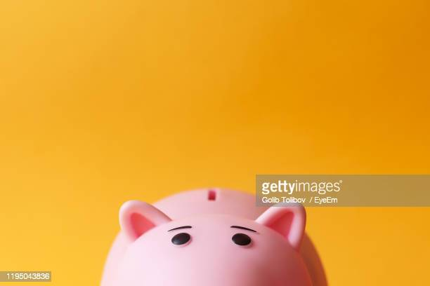 close-up of pink piggy bank against orange background - sparbüchse stock-fotos und bilder