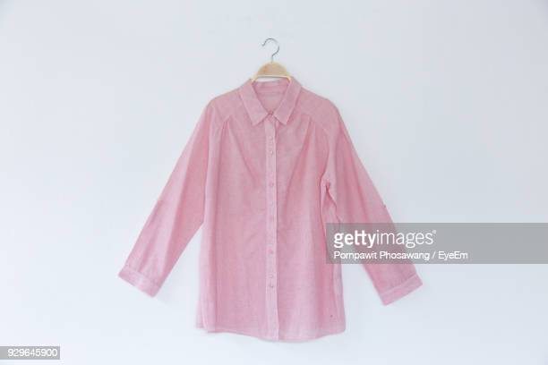 close-up of pink shirt hanging over white background - shirt stock pictures, royalty-free photos & images