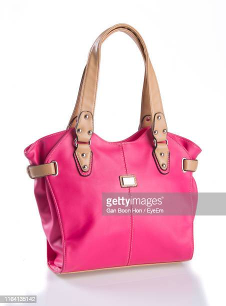 close-up of pink shoulder bag over white background - shoulder bag stock pictures, royalty-free photos & images